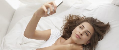 Woman using cell phone on bed